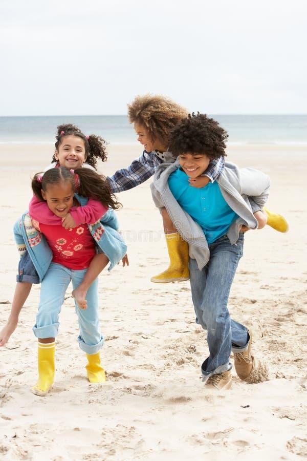 Niños felices que juegan a cuestas en la playa fotografía de archivo libre de regalías