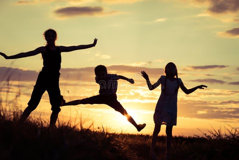 Niños felices que juegan en el parque en el tiempo de la puesta del sol fotografía de archivo