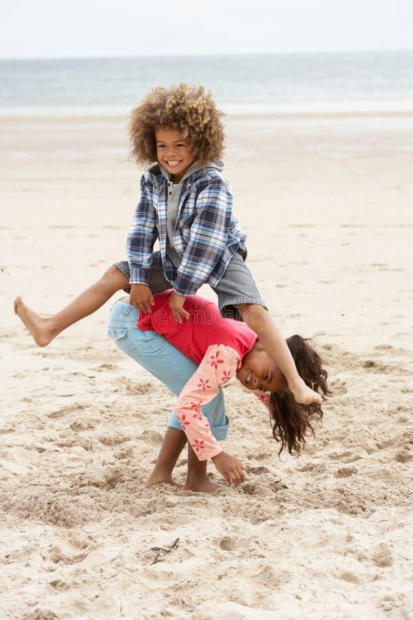 Niños felices que juegan en la playa fotos de archivo