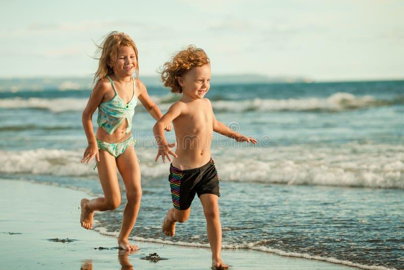 Niños felices que juegan en la playa imagen de archivo