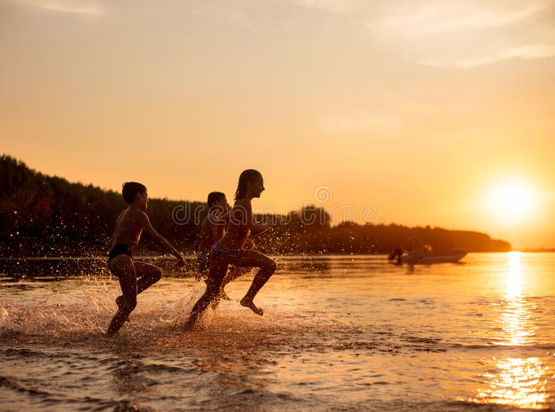 Niños felices que juegan en la playa en el tiempo de la puesta del sol imagen de archivo libre de regalías