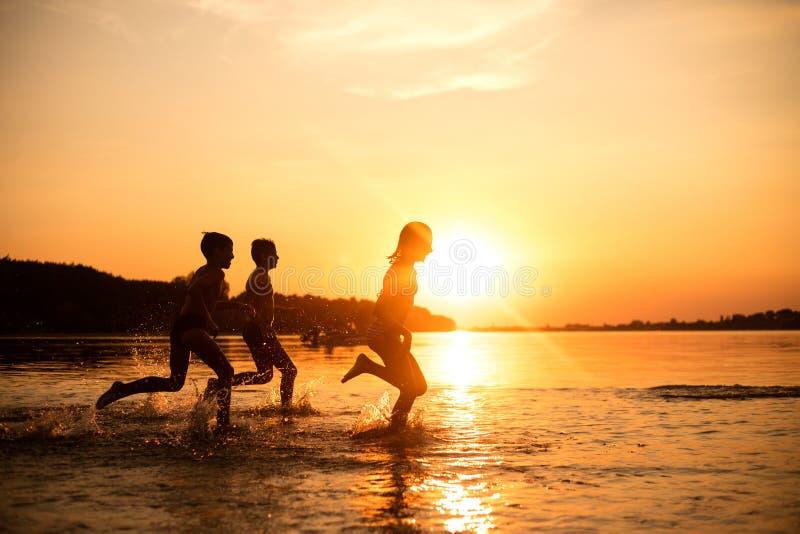 Niños felices que juegan en la playa en el tiempo de la puesta del sol foto de archivo libre de regalías
