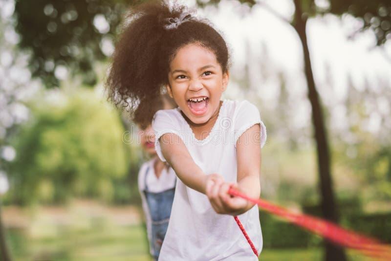 Niños felices que juegan esfuerzo supremo en el parque foto de archivo