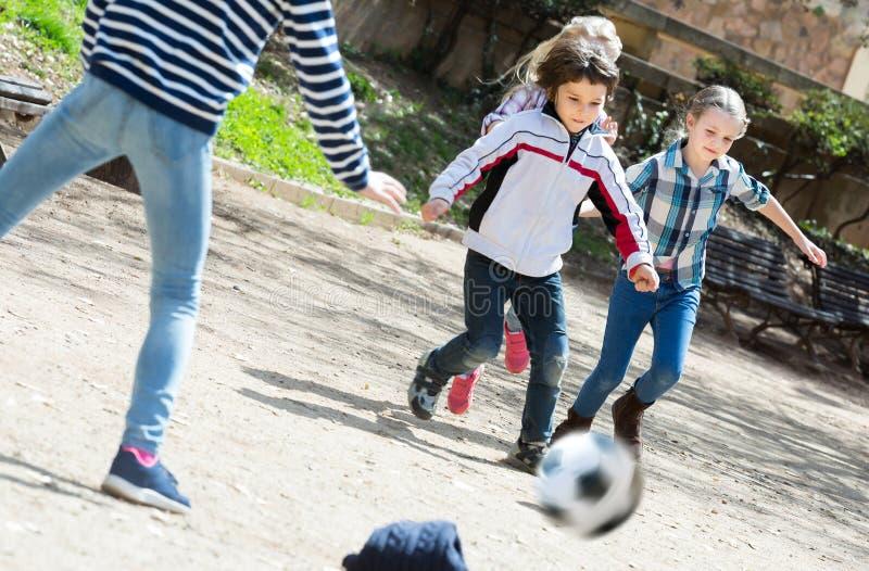 Niños felices que juegan a fútbol de la calle al aire libre imagenes de archivo
