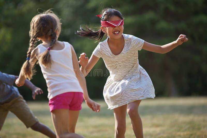 Niños felices que juegan la piel de ante del ` s del hombre ciego foto de archivo