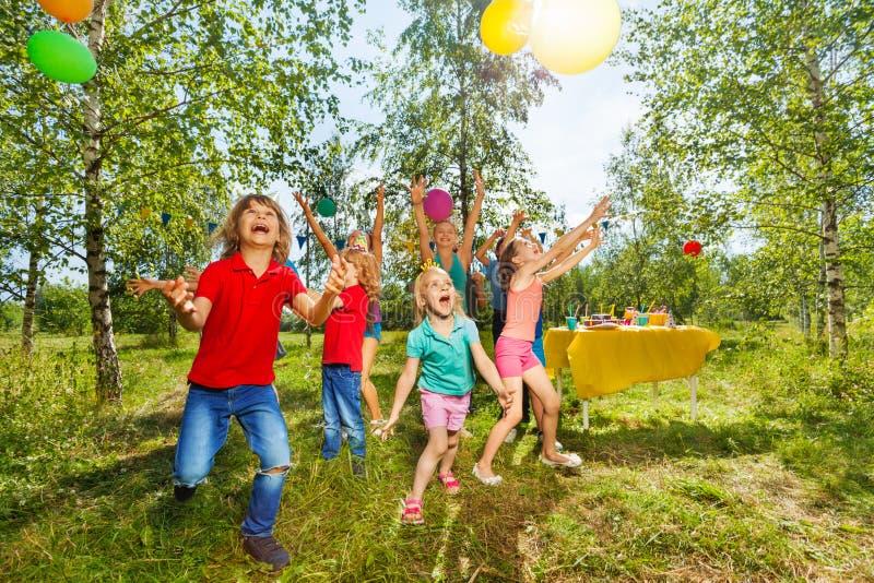 Niños felices que juegan los globos en el parque del verano imagen de archivo