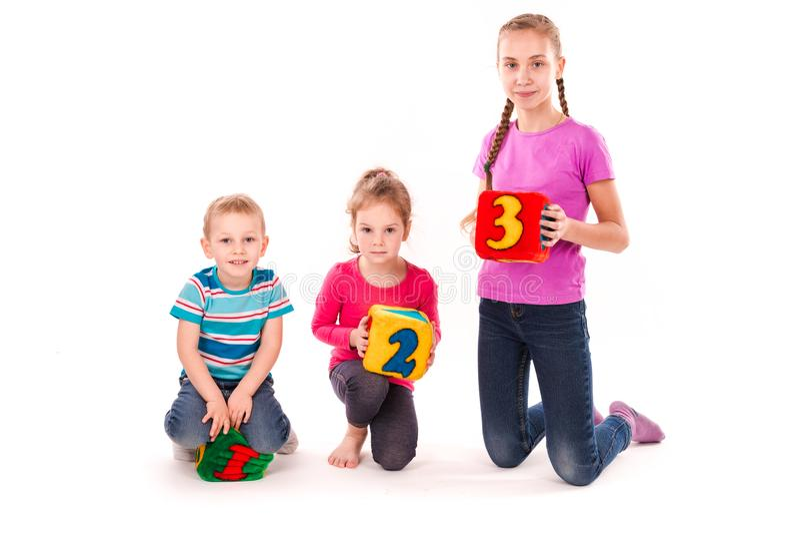 Niños felices que llevan a cabo bloques con números sobre el fondo blanco foto de archivo
