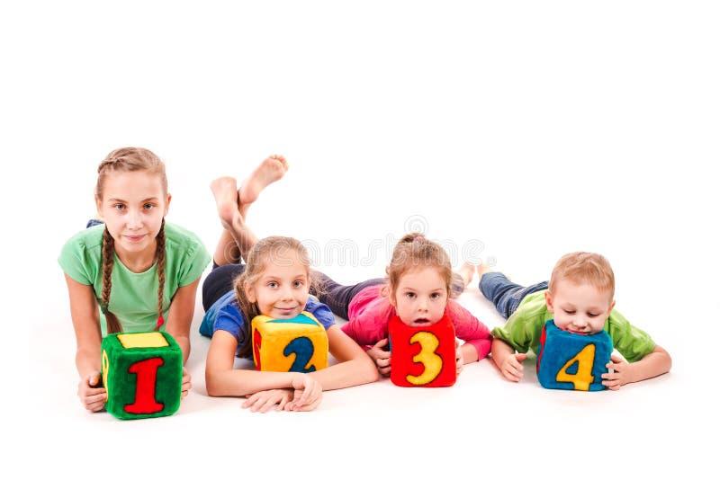 Niños felices que llevan a cabo bloques con números sobre el fondo blanco imagenes de archivo