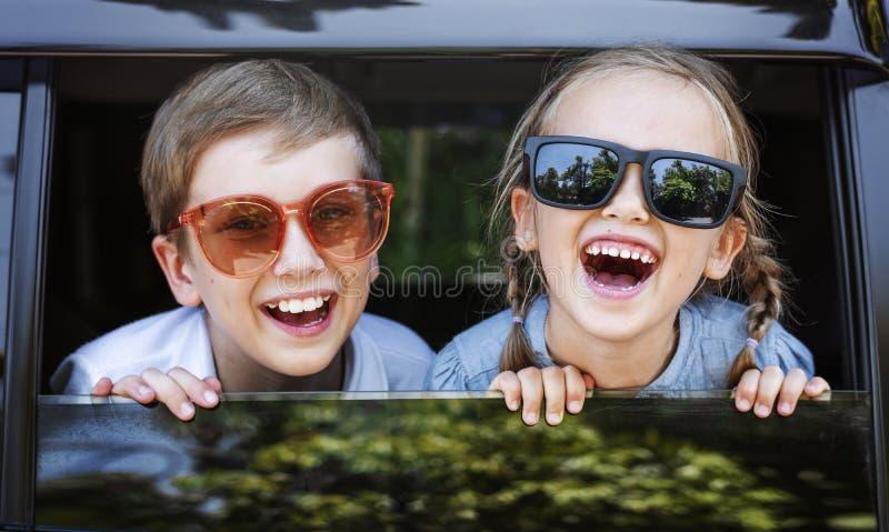 Niños felices que miran hacia fuera la ventanilla del coche foto de archivo libre de regalías