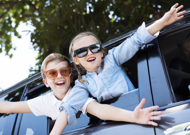 Niños felices que miran hacia fuera la ventanilla del coche imagenes de archivo