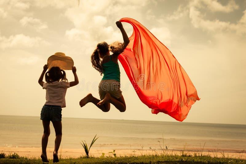 Niños felices que saltan en la playa fotos de archivo