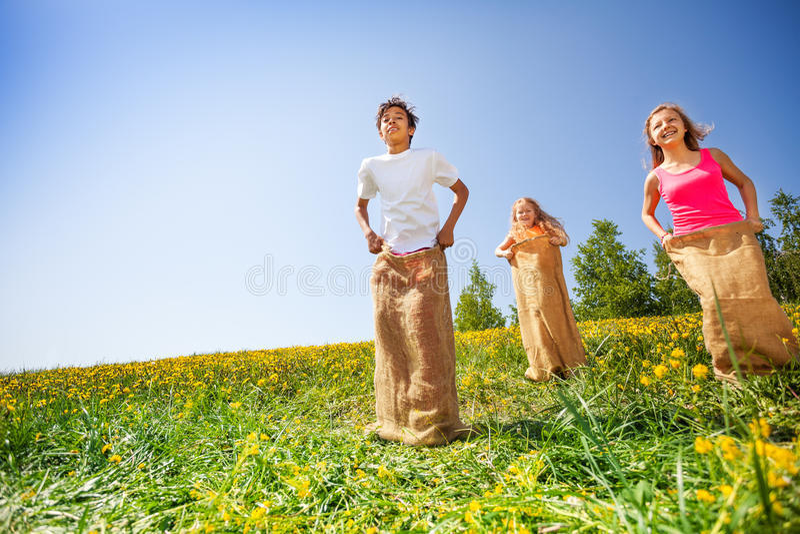 Niños felices que saltan en sacos durante juego fotos de archivo