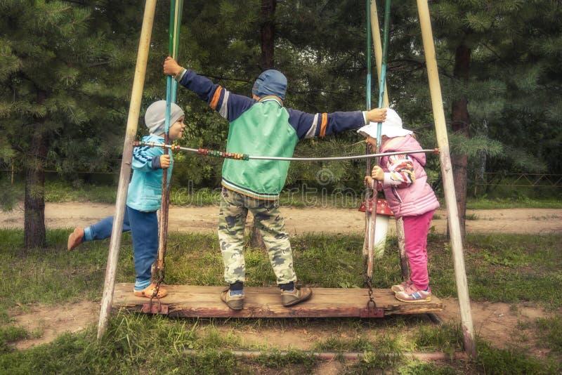 Niños felices que se divierten al aire libre en patio durante vacaciones de verano en el campo que simboliza niñez despreocupada  fotos de archivo