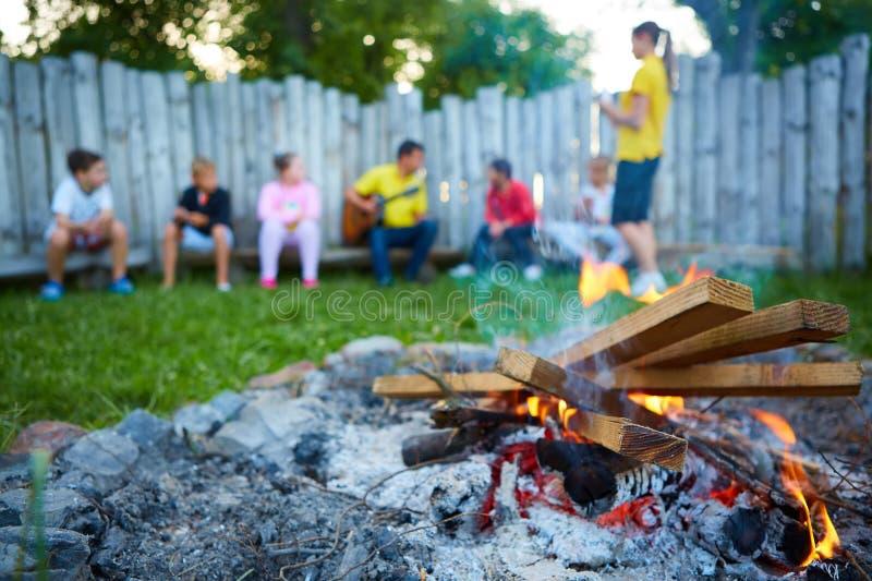 Niños felices que se divierten alrededor del fuego del campo fotos de archivo libres de regalías