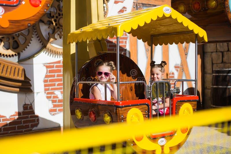 Niños felices que se divierten en el parque de atracciones imagen de archivo libre de regalías
