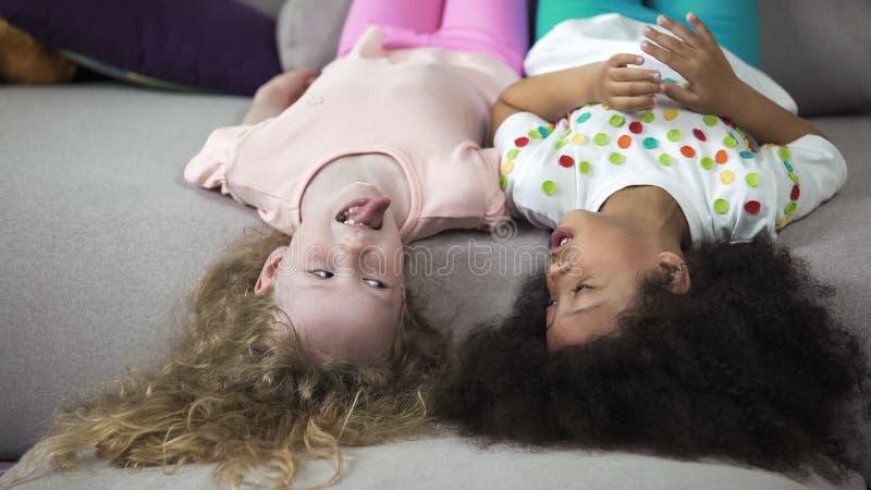 Niños felices que se divierten que miente en el sofá, lengua de la demostración de la muchacha al mejor amigo imagenes de archivo