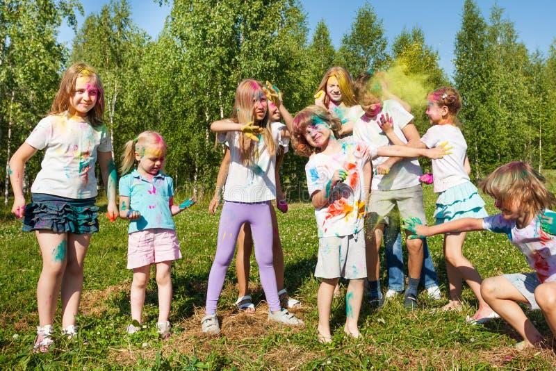 Niños felices que se divierten que celebra festival del color imagen de archivo libre de regalías