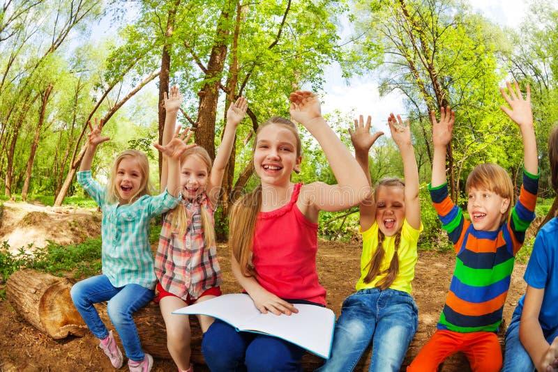 Niños felices que se divierten que lee un libro en el bosque fotos de archivo