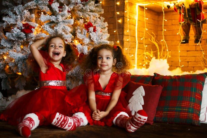 Niños felices que se sientan en el piso cerca de un árbol de navidad y de una chimenea Hermanas gemelas sonrientes en vestido roj fotografía de archivo libre de regalías