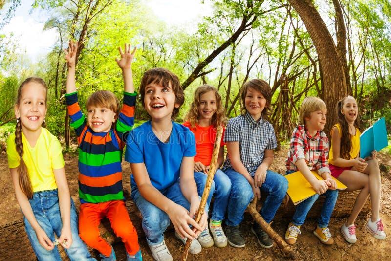 Niños felices que se sientan en un registro y los libros de lectura fotos de archivo libres de regalías