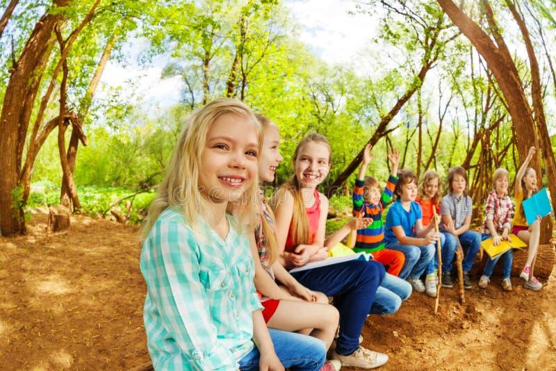 Niños felices que sientan en un inicio de sesión el campamento de verano fotografía de archivo libre de regalías
