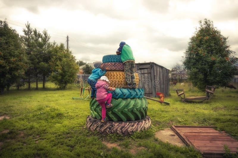 Niños felices que tienen patio del aire libre de la diversión durante vacaciones de verano en el campo que simboliza niñez despre imágenes de archivo libres de regalías