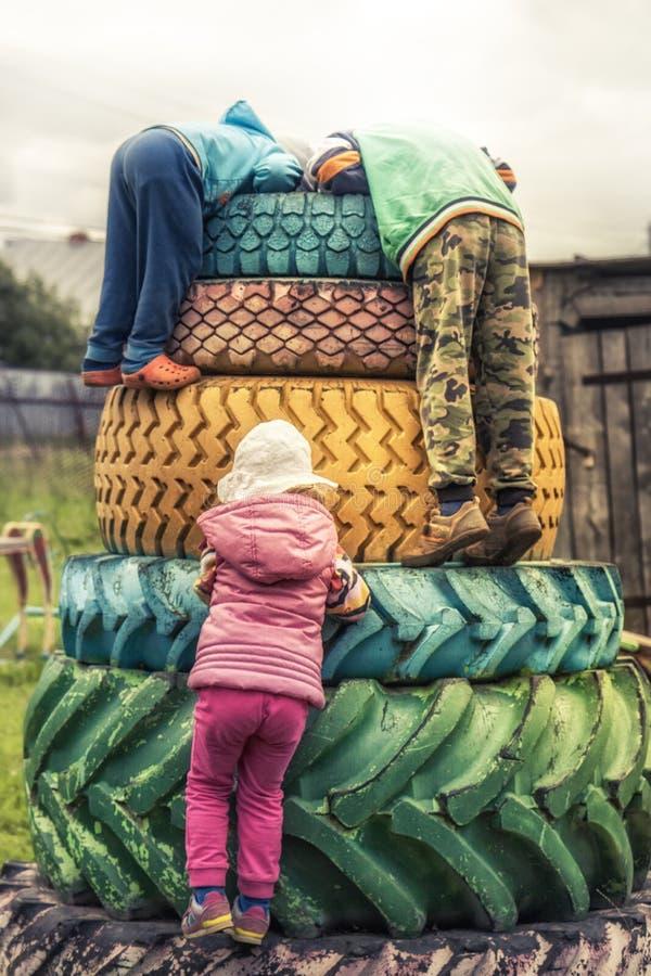 Niños felices que tienen patio del aire libre de la diversión durante vacaciones de verano en el campo que simboliza niñez despre fotos de archivo