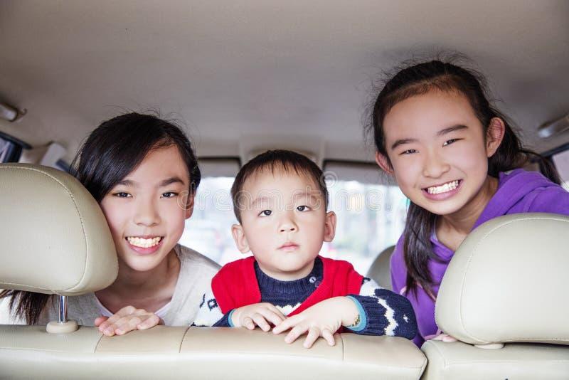 Niños felices que viajan en el coche foto de archivo