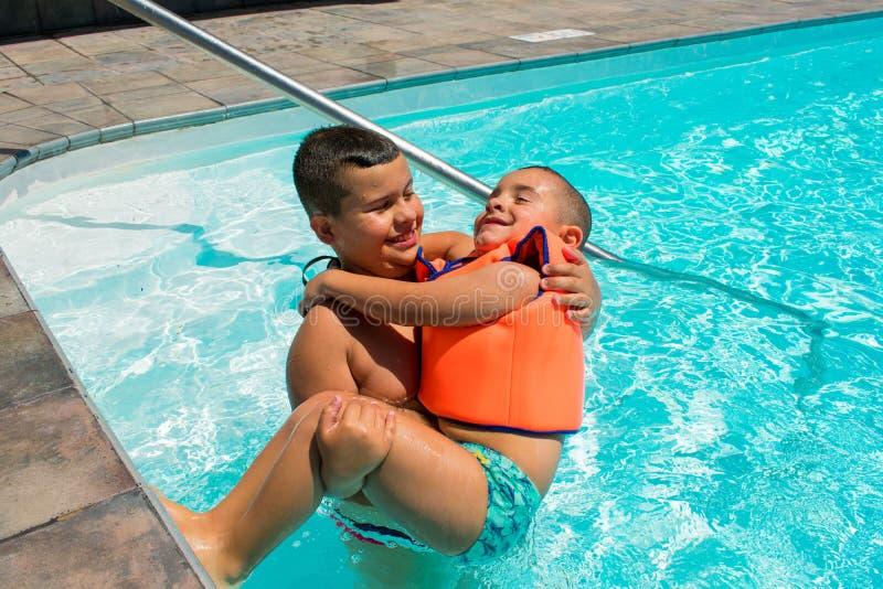Ni?os felices s en la piscina imágenes de archivo libres de regalías
