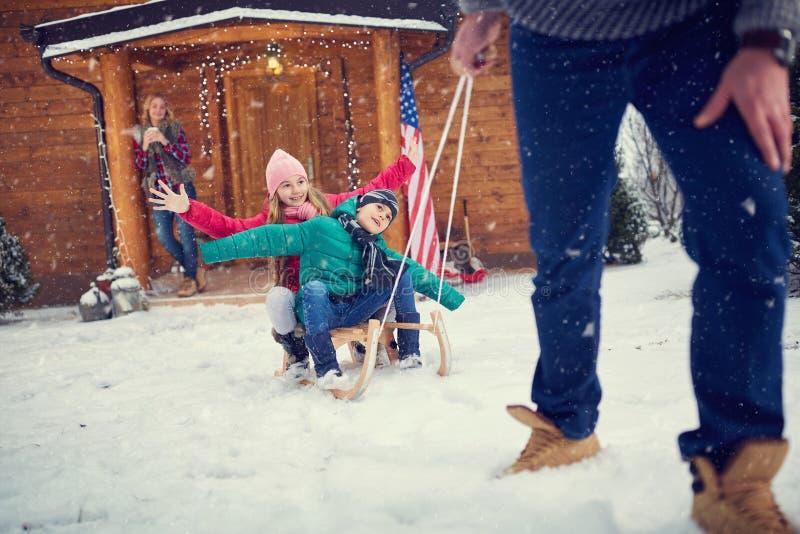 Niños felices sledding en invierno imágenes de archivo libres de regalías