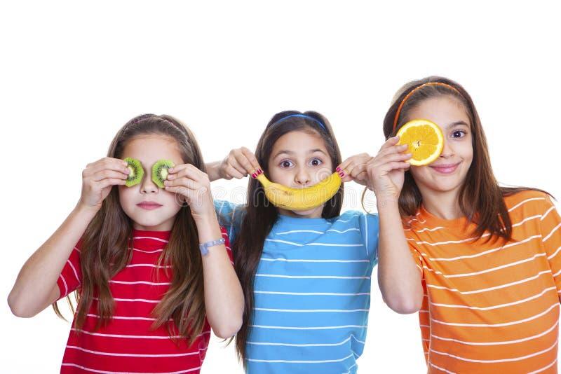 Niños felices sonrientes con comida saludable de frutas imágenes de archivo libres de regalías