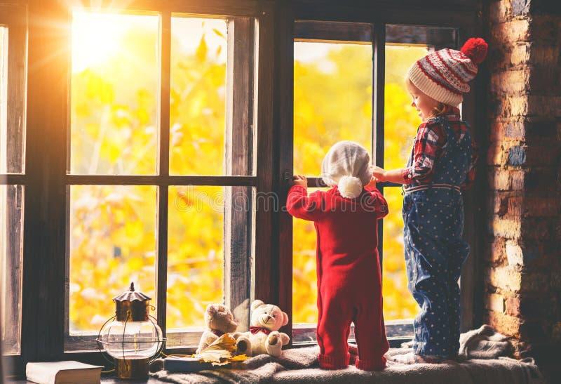 Niños hermano y hermana que admiran la ventana para el otoño foto de archivo