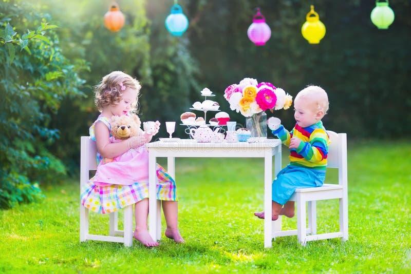 Niños hermosos en la fiesta del té de la muñeca fotografía de archivo