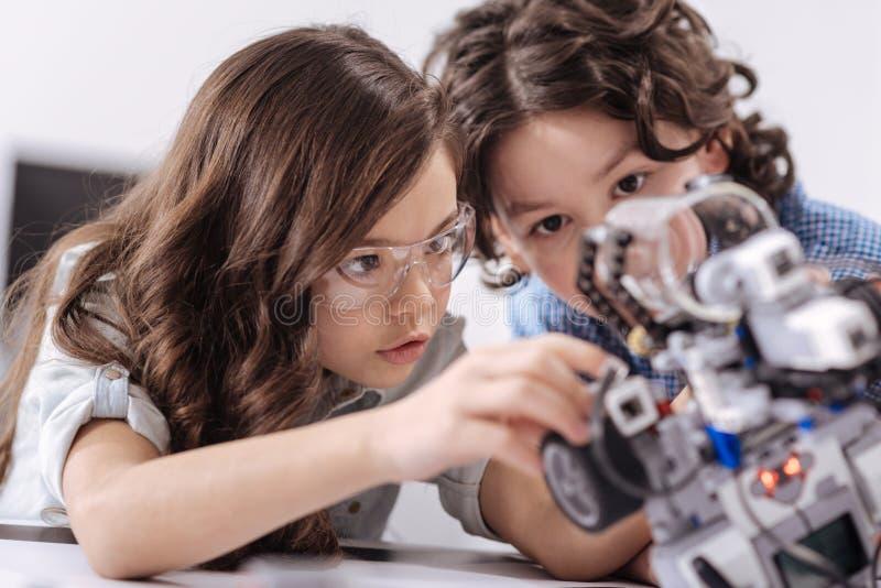 Niños inventivos que disfrutan de la lección de la ciencia en la escuela imagenes de archivo