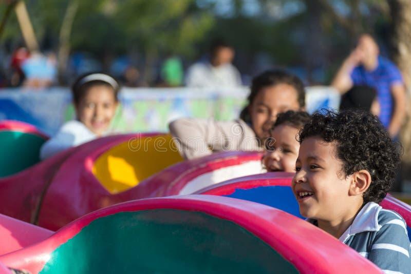 Niños jovenes felices en el parque de atracciones imagen de archivo libre de regalías