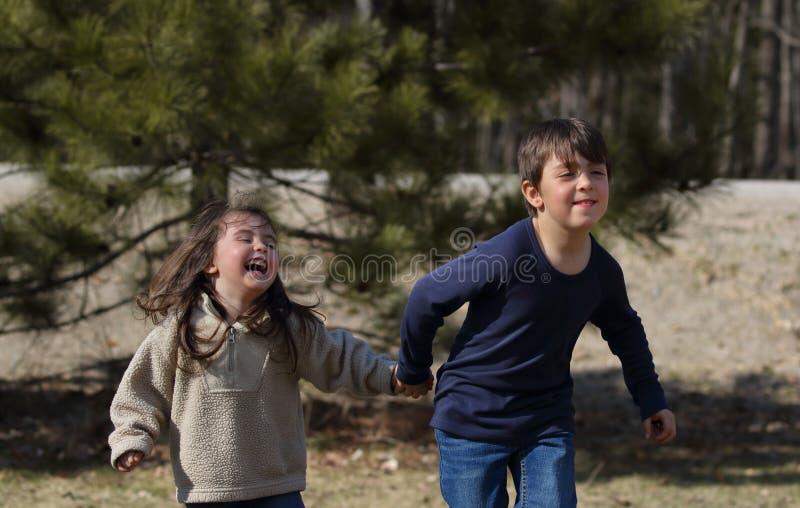 Niños jovenes que corren durante la primavera imágenes de archivo libres de regalías