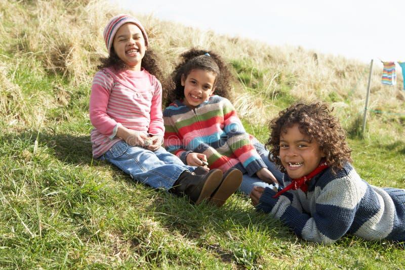 Niños jovenes que se sientan afuera en parque de la caravana foto de archivo