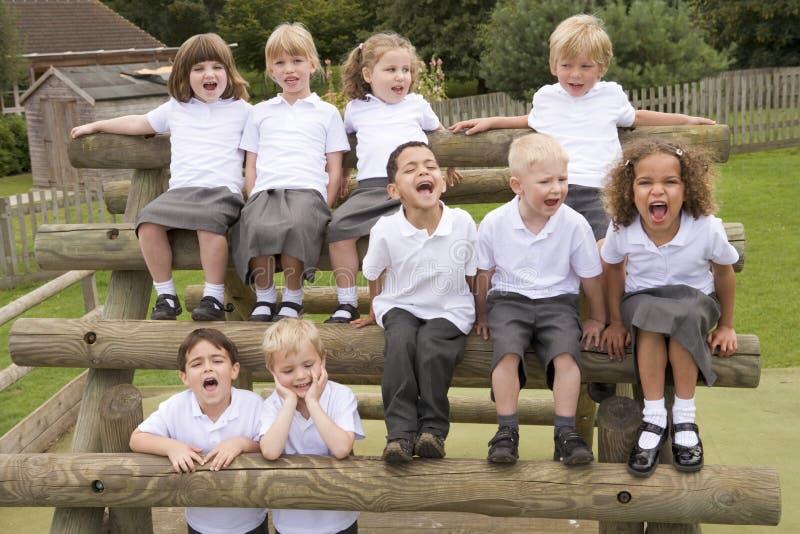 Niños jovenes que se sientan en bancos y la griterío imagen de archivo