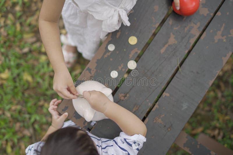 Niños juntas que ponen monedas en la hucha fotos de archivo