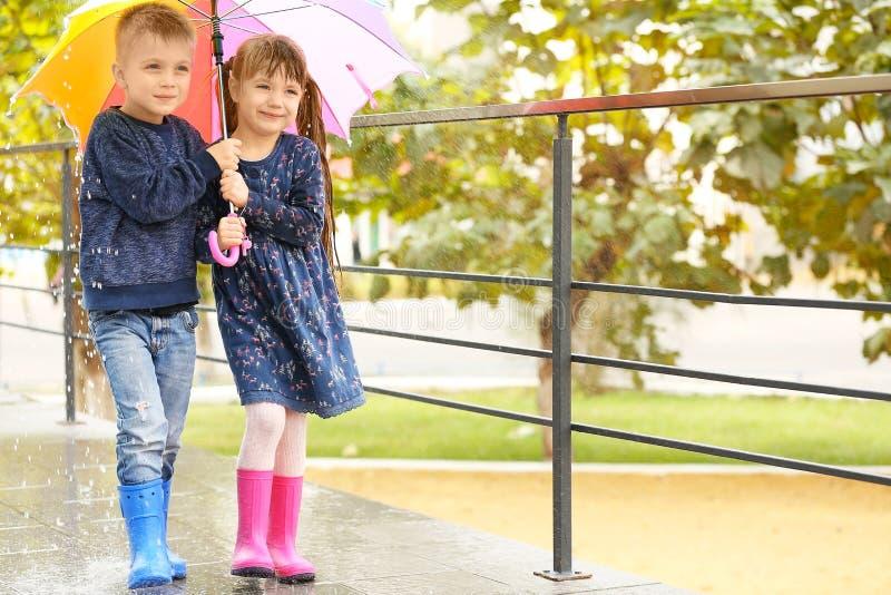 Niños lindos debajo del paraguas colorido imagen de archivo
