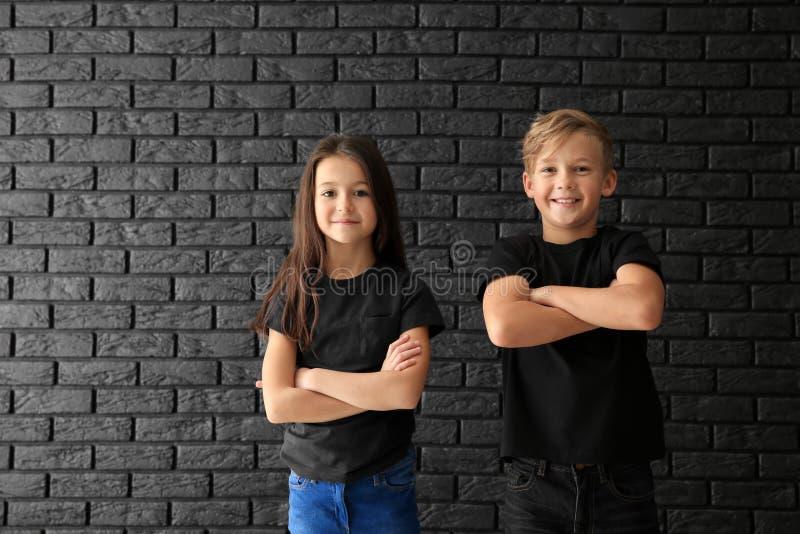 Niños lindos en camisetas contra la pared de ladrillo oscura fotografía de archivo libre de regalías
