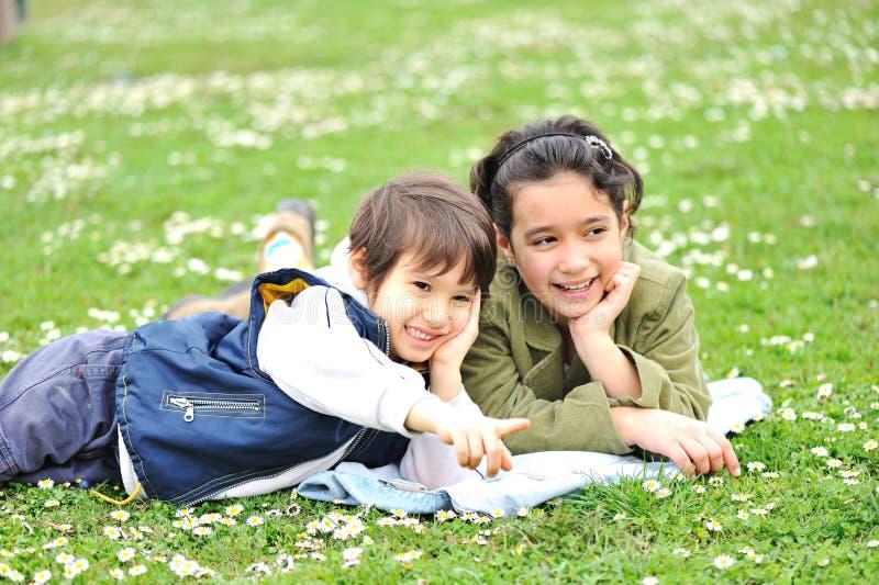 Niños lindos en prado imagenes de archivo