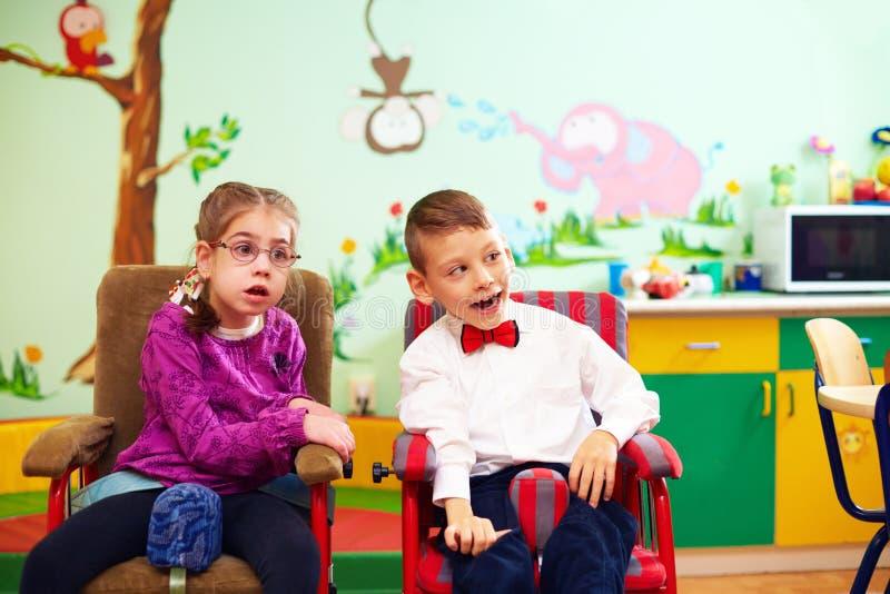 Niños lindos en sillas de ruedas en la guardería para los niños con necesidades especiales foto de archivo libre de regalías