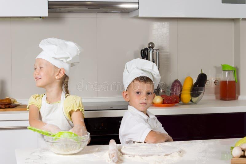 Niños lindos en traje de los cocineros en cocina imágenes de archivo libres de regalías