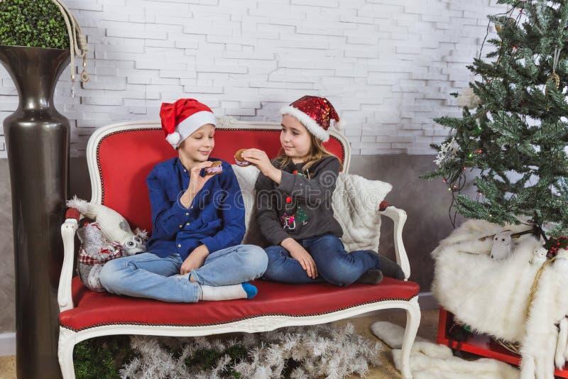 Niños lindos felices en los sombreros de Papá Noel que comen las galletas deliciosas en casa fotos de archivo libres de regalías