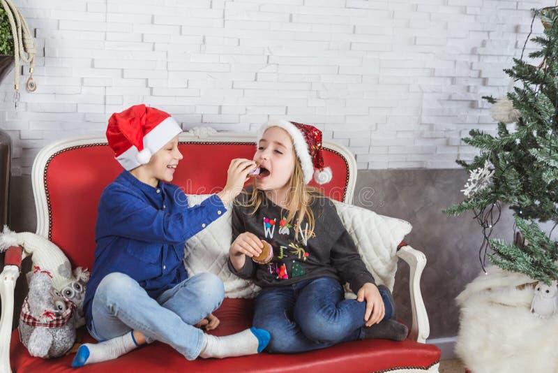 Niños lindos felices en los sombreros de Papá Noel que comen las galletas deliciosas en casa foto de archivo libre de regalías