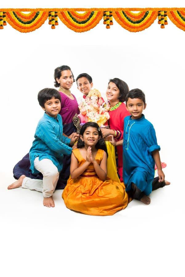 Niños lindos indios que sostienen la estatua de Lord Ganesha o de Ganapati en el festival o el chaturthi de Ganesh, acogiendo con imágenes de archivo libres de regalías