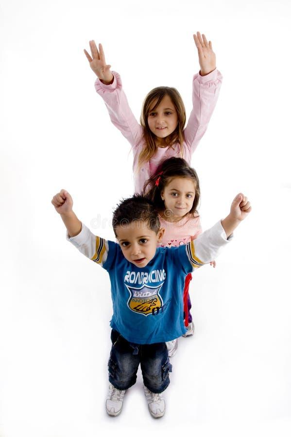 Niños lindos juguetones que se colocan en fila fotografía de archivo