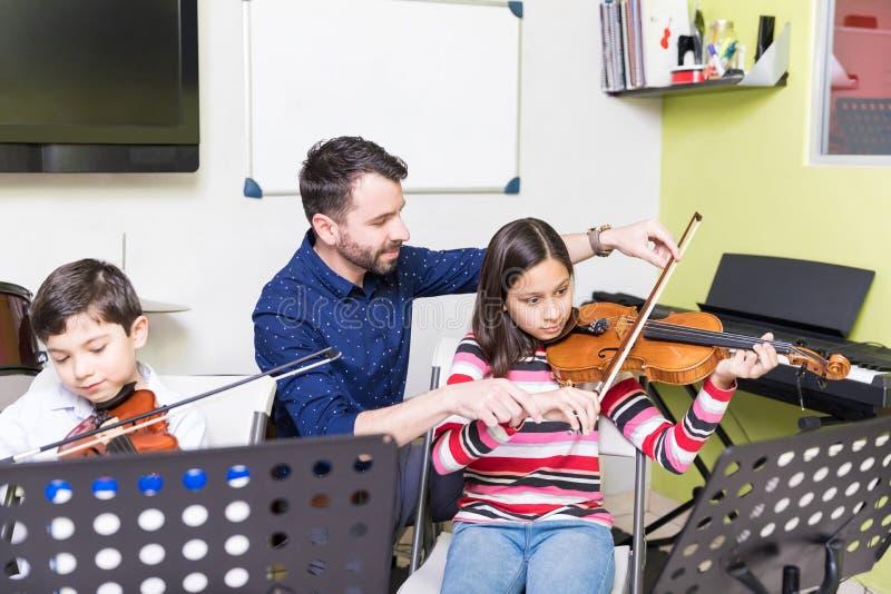 Niños lindos que aprenden tocar el violín en clase imagen de archivo libre de regalías