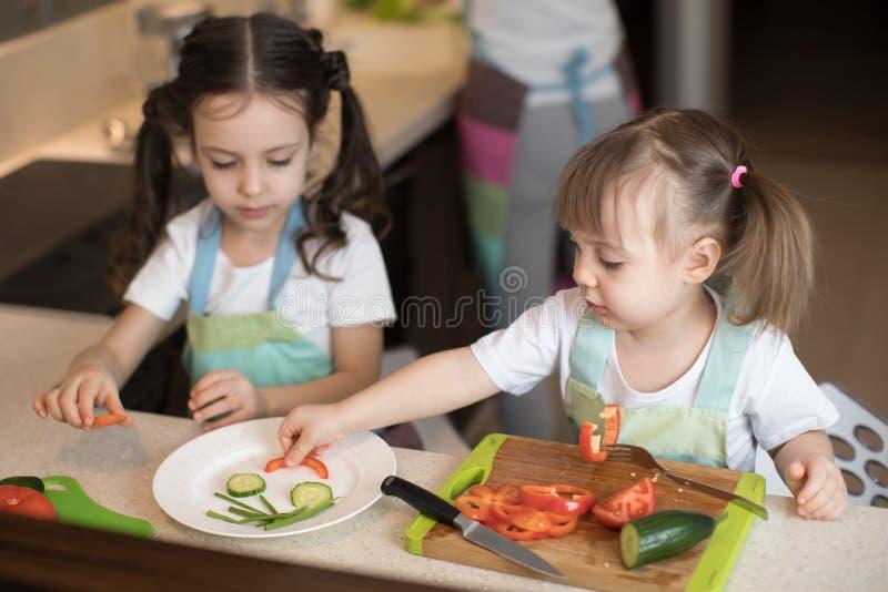 Niños lindos que ayudan a la madre en la cocina Hermanas adorables que hacen la cara divertida con las verduras en la placa foto de archivo